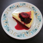 Parisian flan slice with berry coulis on top, on a plate