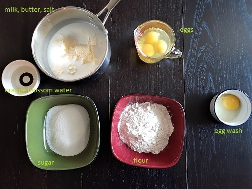 Prep to make a galette franc-comtoise - a mix between flan and chou pastry : Pot with milk, salt and butter ; cup with eggs ; bowl with orange blossom water ; bowl with sugar ; bowl with flour ; bowl with egg wash
