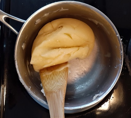 Drying out the pastry dough in a pot with a wooden spoon