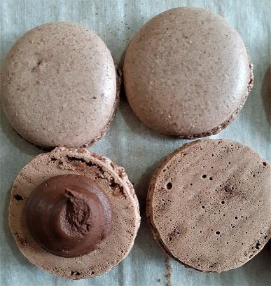 Vegan chocolate macaron shells, one garnished with a chocolate ganache