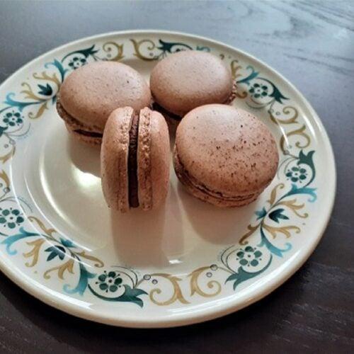 Four vegan chocolate macarons on a plate