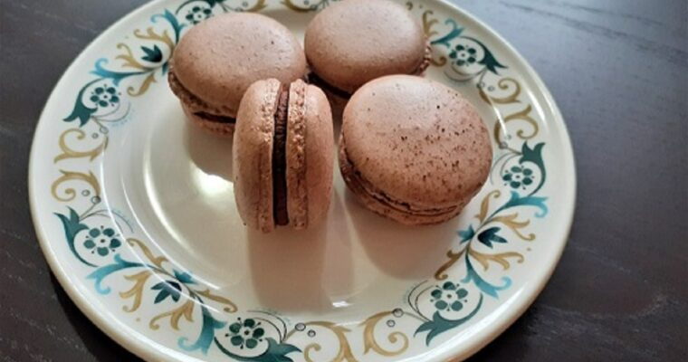 Four vegan chocolate macarons on a plate