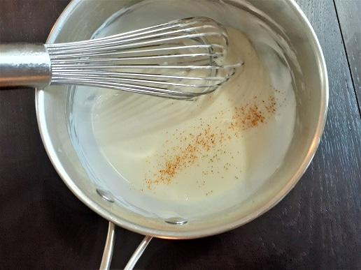 Bechamel sauce in a pot with a whisk