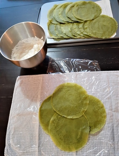 Matcha crepe cake building : matcha crepes on a tray, chantilly in a bowl, four crepes on a dish towel with plastic wrap