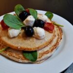 Oatmeal and egg white pancakes with mozzarella, cherry tomatoes and baby spinach on a plate.