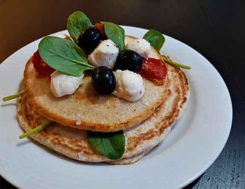 Low-carb and delicious oatmeal pancakes with mozzarella, cherry tomatoes and baby spinach, on a plate