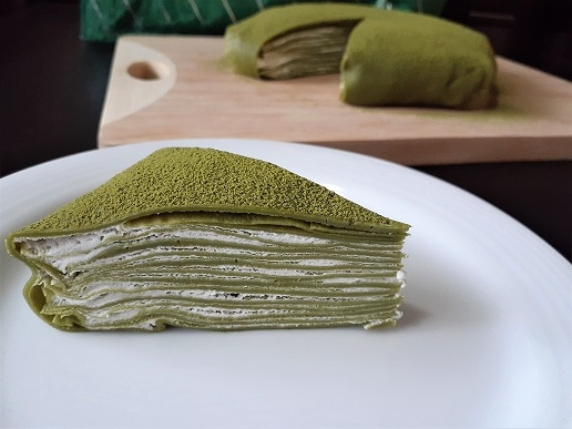 Matcha crepe cake slice on a plate with the rest of the cake in the background