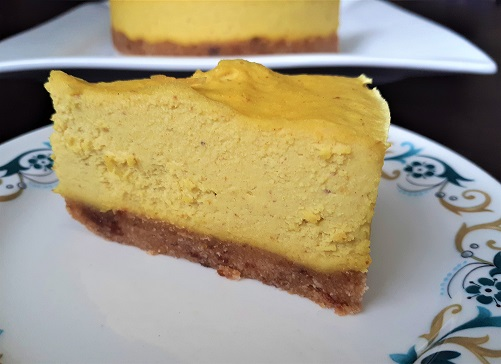 Vegan lemon cheesecake slice on a small plate. Whole cheesecake in the background.