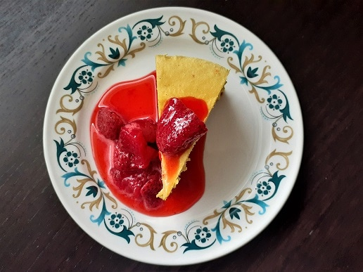 Vegan lemon cheesecake - raw, no sugar, GF - on a plate with a strawberry coulis