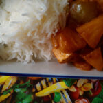 Pineapple tofu in a sweet and sour sauce, served with rice on a rectangular plate.