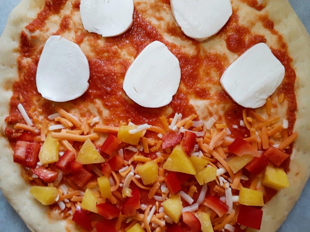 Pizza before baking, half side Margherita, half side Hawaiian