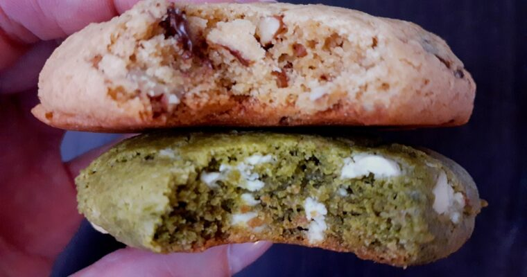 2 fingers holding 2 chickpea flour cookies, one is matcha and white chocolate, the other is a turtle cookie