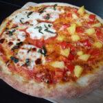 Half margherita, half hawaiian vegetarian pizza on a wooden board