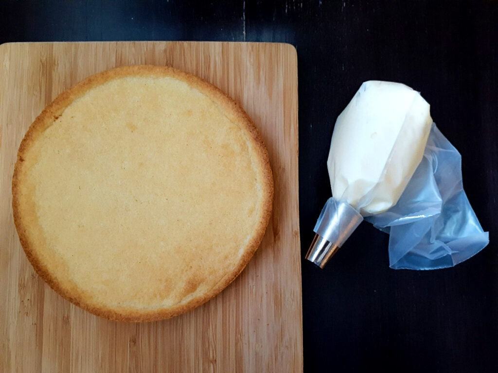 Baked buttery tart crust on a wooden board and a piping bag filled with pastry cream next to it