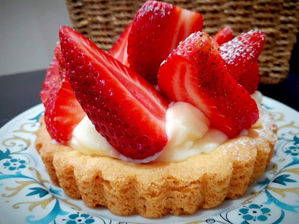 Small strawberry tart on a plate, with a basket in the background