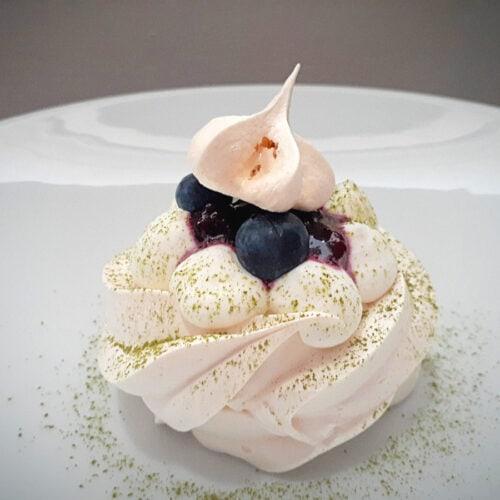Mini pavlova with blueberry sauce on a white plate