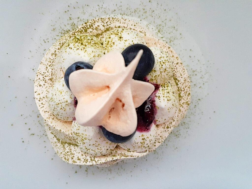 Mini pavlova with whipped cream, blueberry sauce, fresh blueberries, matcha powder and a star meringue
