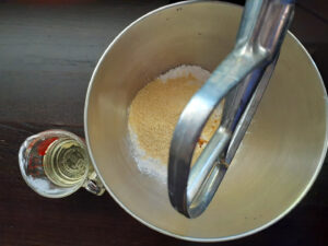 Bowl with paddle attachment with dry ingredients, oil in a cup