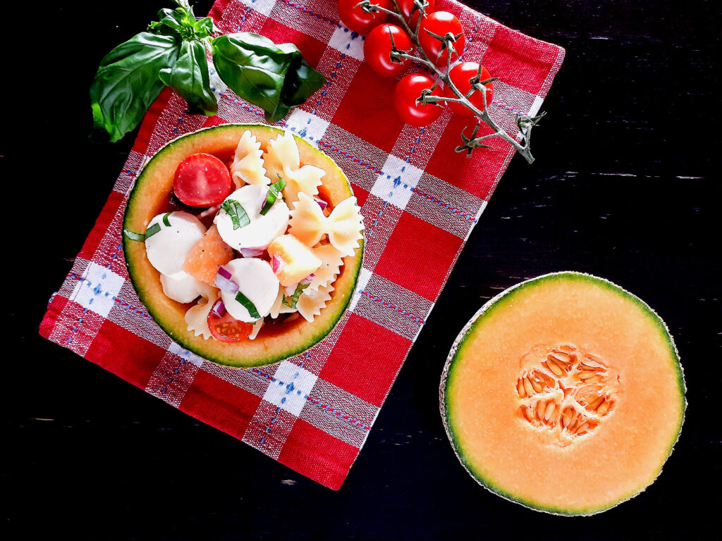 Pasta salad in a melon-half on a table cloth, with a cherry tomato grape, basil leaves and a melon half on the side