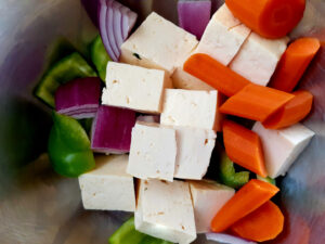 Carrots, red onions, pepper and tofu cut in a bowl