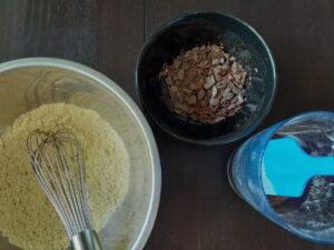 Dry ingredients with a bowl with a whisk, wet ingredients in a jug with a spatula, chocolate chips in a bowl