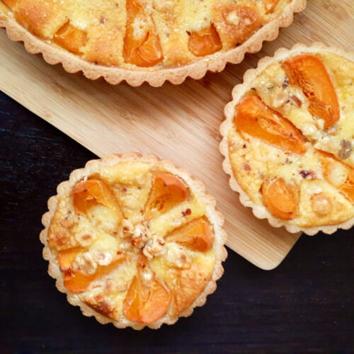 Two small and one big apricot tarts on a wooden board