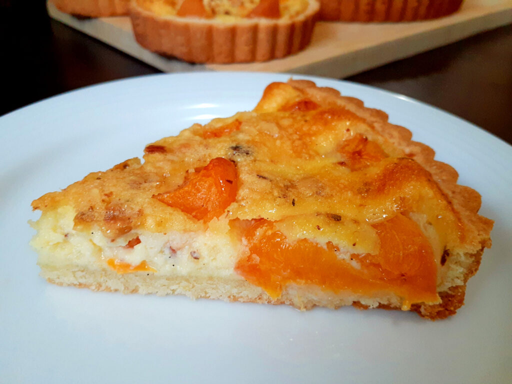 Slice of apricot tart on a plate with apricot tarts in the background.