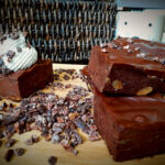 Sweet potato brownies with cocoa nibs on a wooden board. Mug and wicker basket in the background.