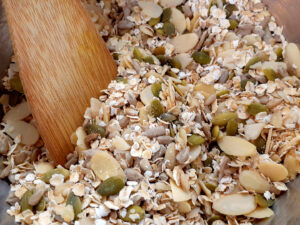 Oats, nuts and seeds in a bowl with a wooden spoon