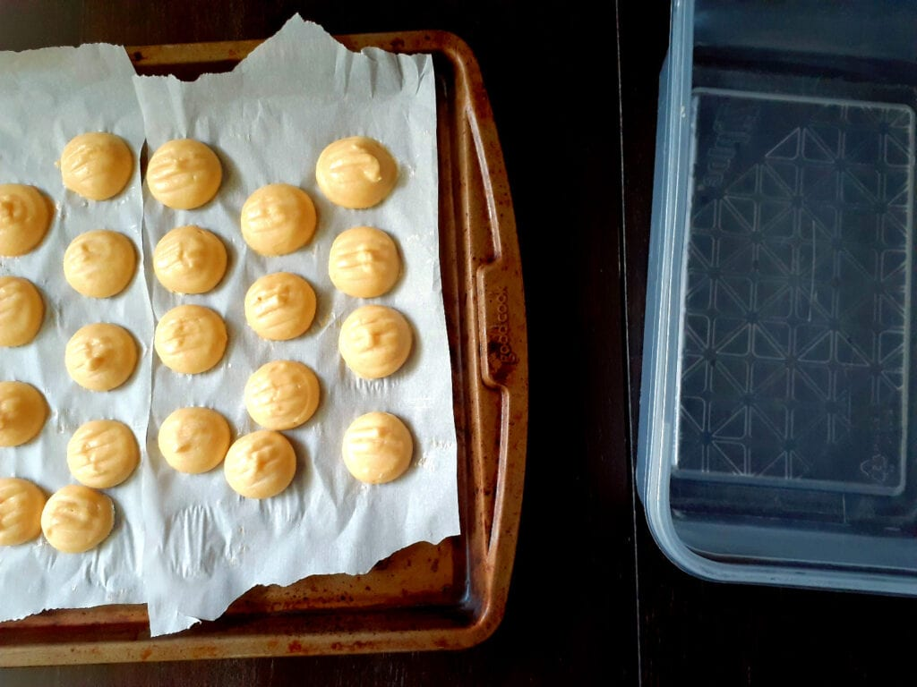raw choux on a baking sheet lined with parchment paper, empty container next to it