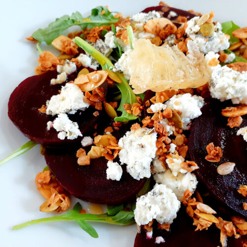 Vegetarian beet salad with goat cheese, granola, arugula and raw honeycomb