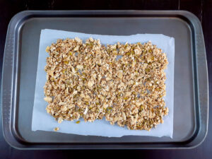 granola on a baking sheet lined with parchment paper, before baking