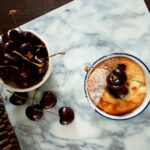 cherry clafoutis in a ramekin with a small bowl of cherries and 4 cherries on the table