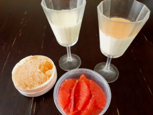 Two wine glasses with panna cotta, raw honeycomb and grapefruit segmentd on the side