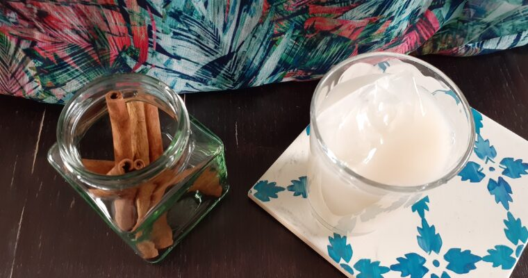 Glass of horchata, jar with cinnamon sticks