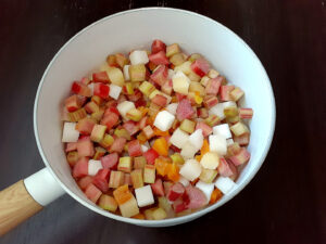 Rhubarb and dried apricot cubes, orange juice and sugar cubes in a pot