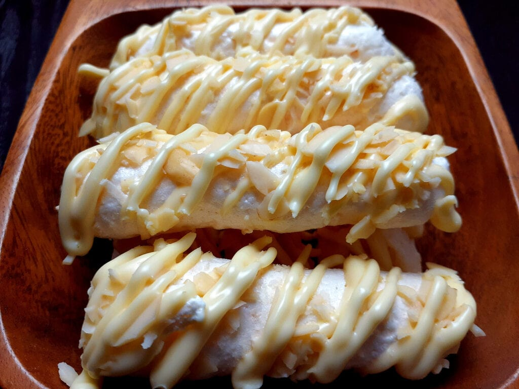 Coconut meringue sticks drizzled with white chocolate and sprinkled with almonds