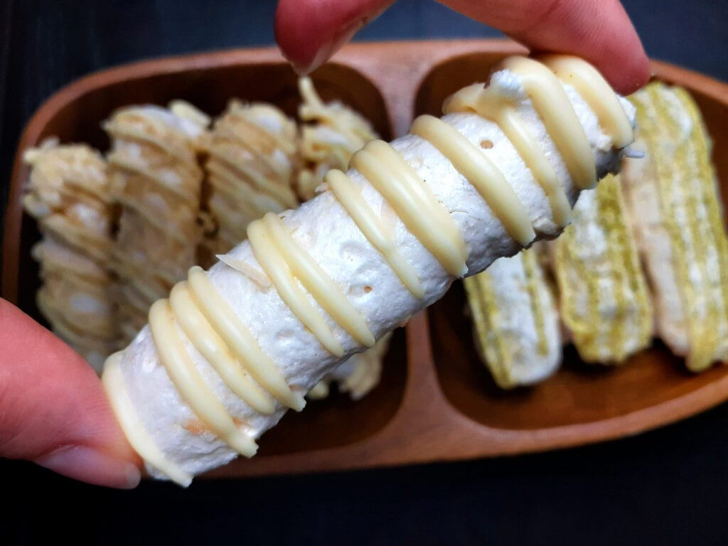 Coconut meringue sticks with one being held with two fingers
