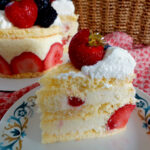 Slice of fraisier on a plate with cake in the background