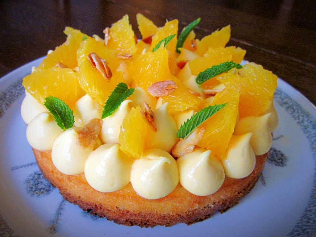 Fantastik cake with passion curd, candied almonds, orange supremes and mint leaves.