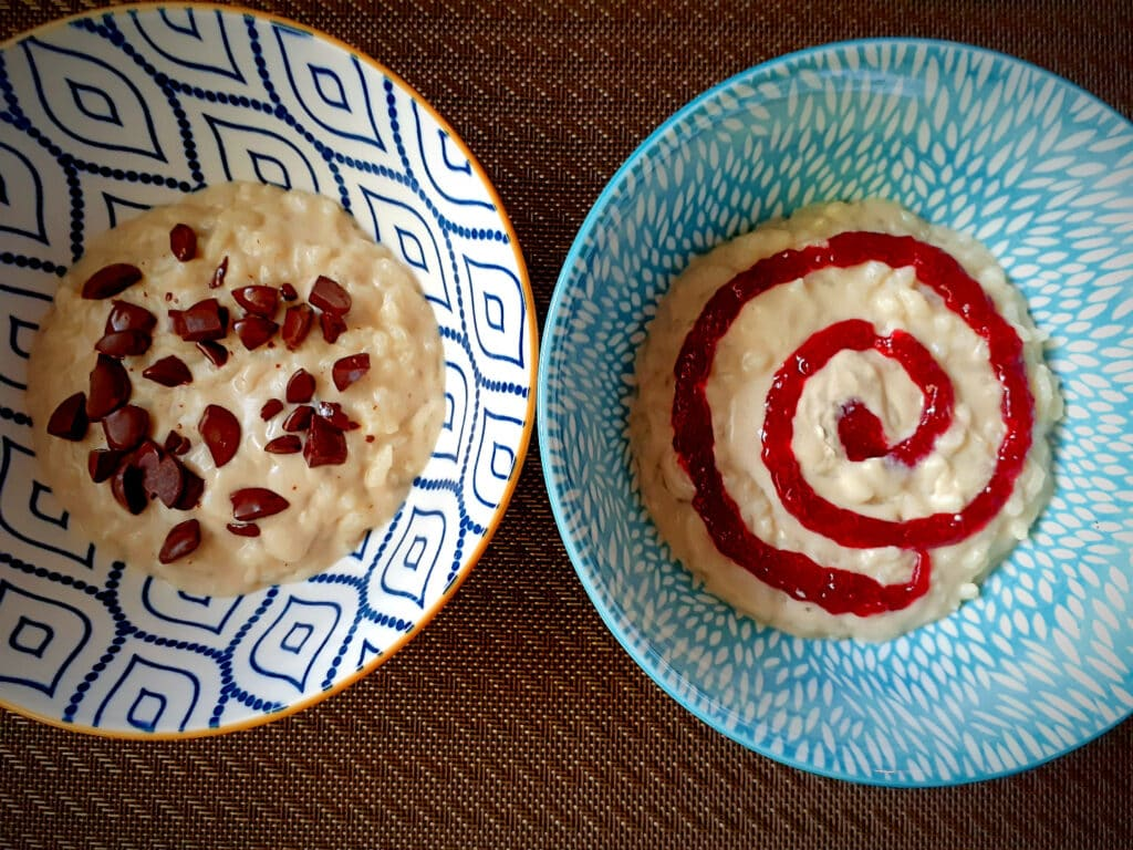 two bowls of rice pudding, one with chocolate chips and the other with a raspberry jam spiral