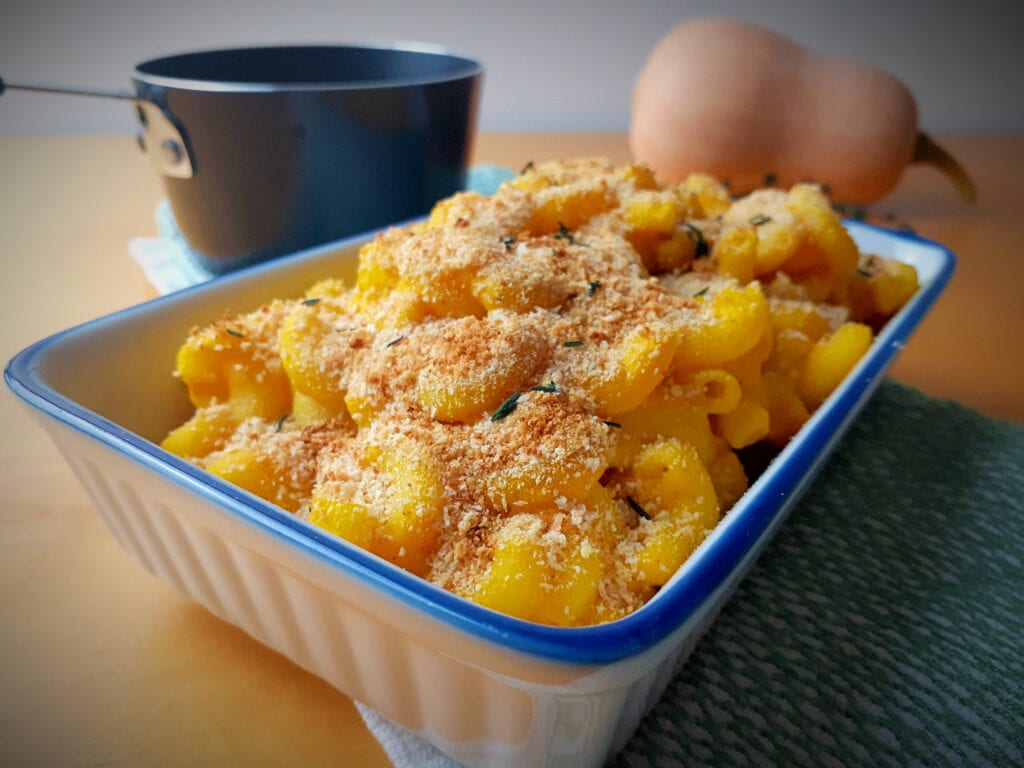vegan macaroni and cheese in a rectangular dish with breadcrumbs and thyme on top. Small pot and butternut in the background.