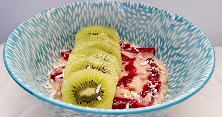 Rice pudding bowl with raspberry jam, kiwi fruit slices and shredded coconut