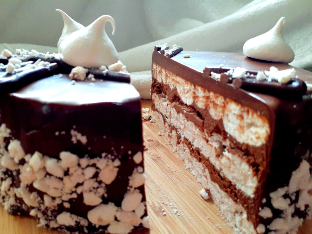 Cinnamon meringue and chocolate cake cut in half on a wooden board