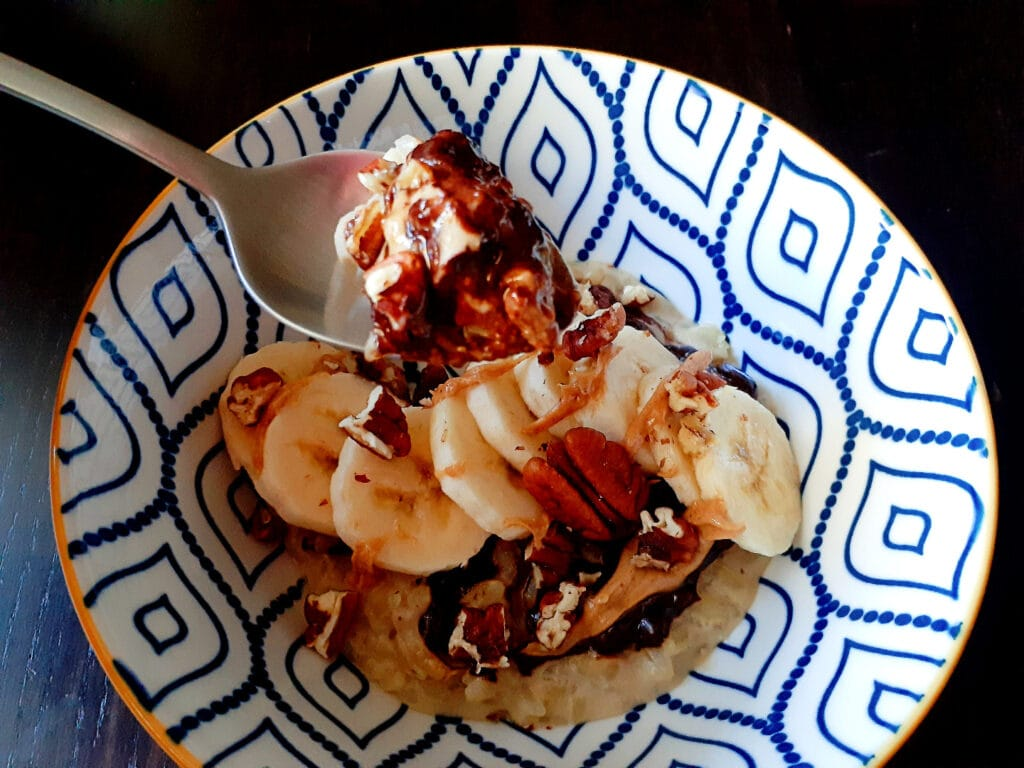 Rice pudding with dark chocolate chips, banana slices, pecan and peanut butter