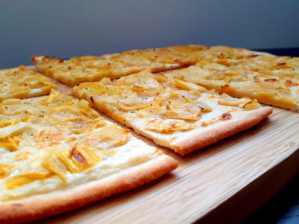 Flammekueche cut in 8 slices on a wooden board.