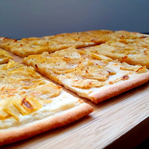 Flammekueche cut in slices on a wooden board