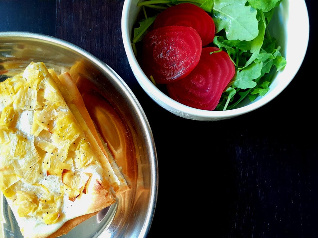 Flammekueche slices on top of each others in a pan and a bowl of arugula with sliced beets.