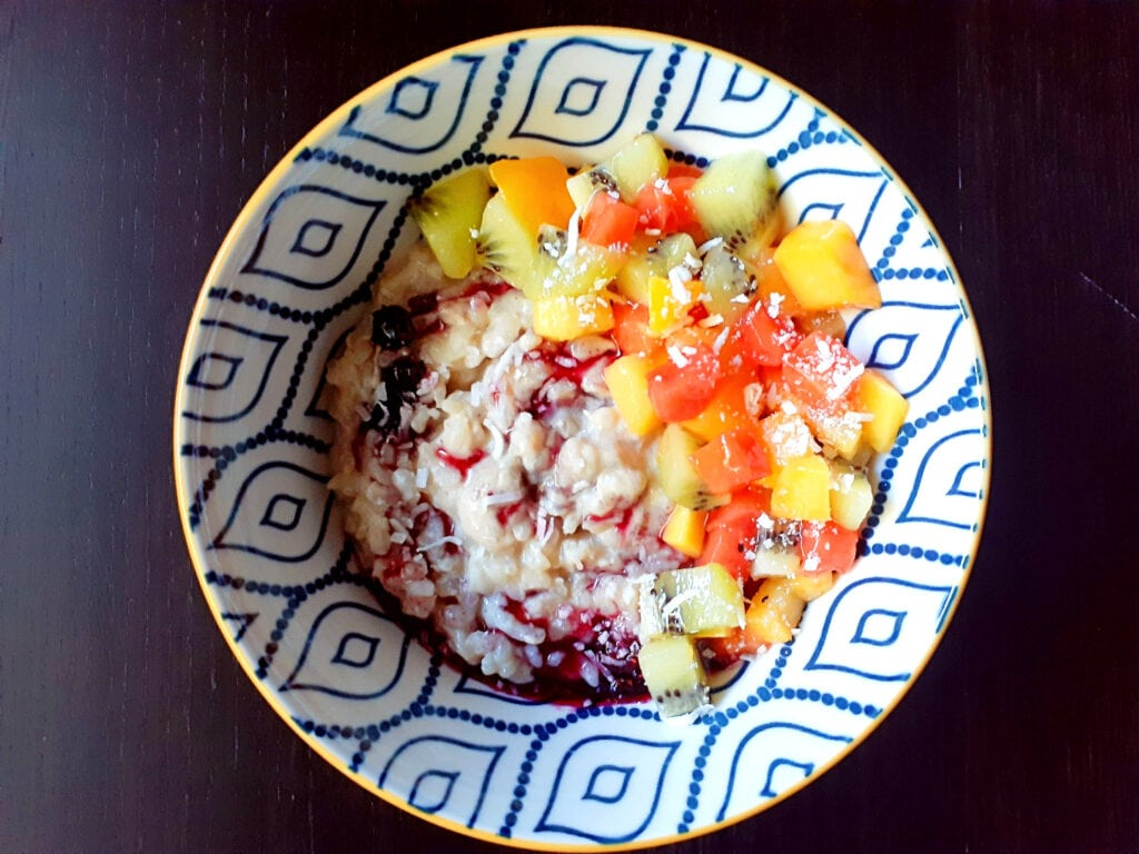 Rice pudding with berry sauce, exotic fruits and shredded coconut