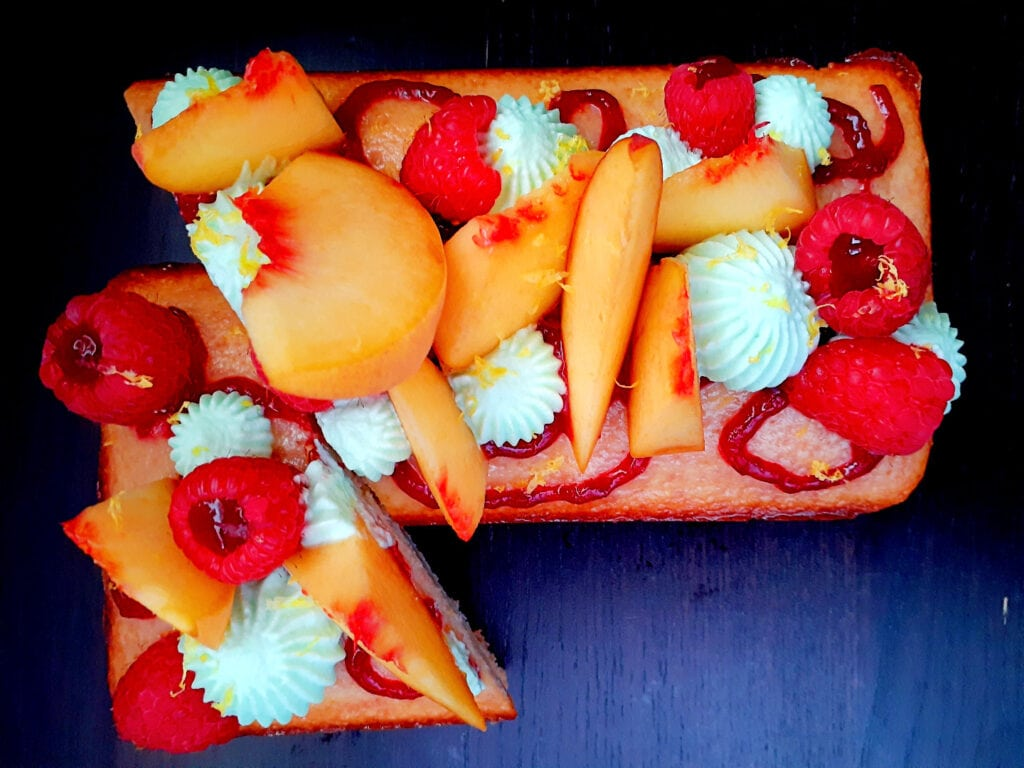 Peach, verbena and raspberry tart cut diagonally